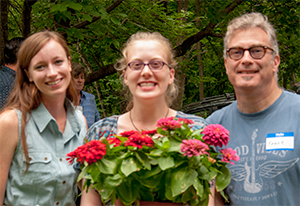 Special student volunteer Amanda Ostella (center) was honored with a special dish of flower selected for her by GSWA staff member Kelly Martin (left). Here the two stand with Amanda's proud father. Credit: GSWA/S. Reynolds